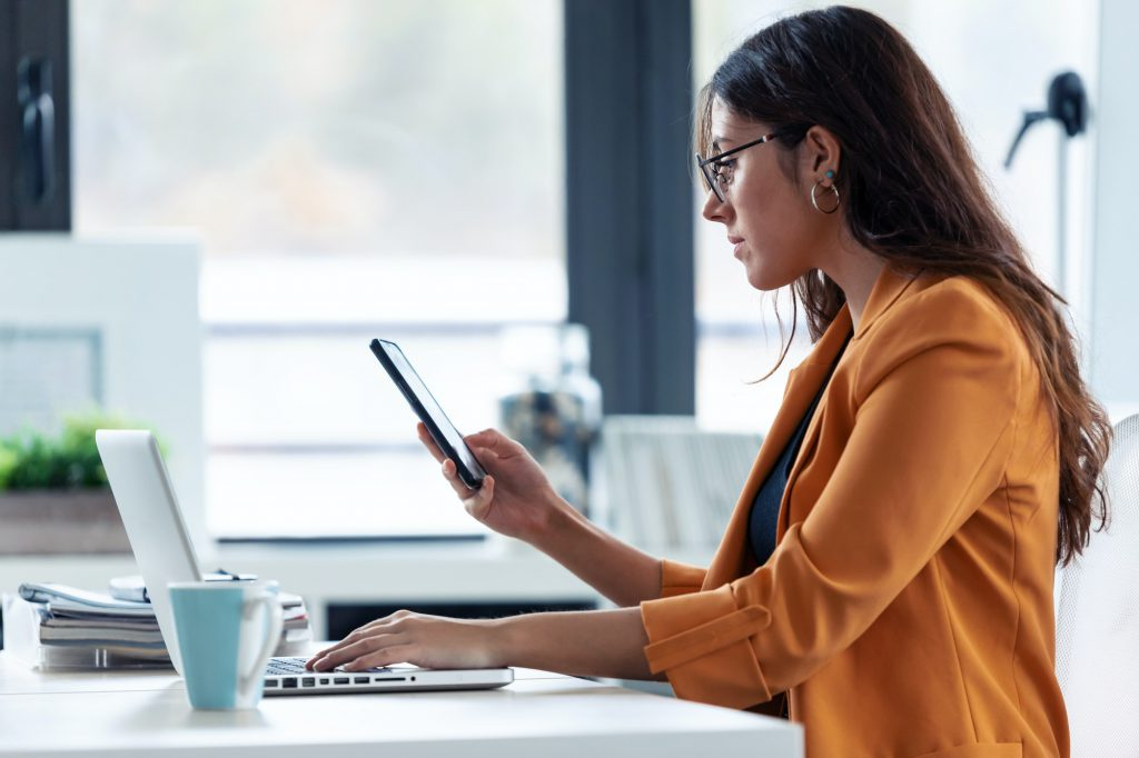 Business young woman using her mobile phone while working with laptop in the office.